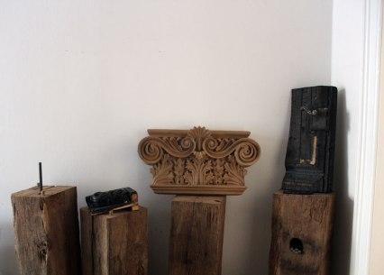 I campioni carbonizzati prelevato dall'Am Hof di Vienna e al centro un capitello di lesena ricostruito sugli originali
